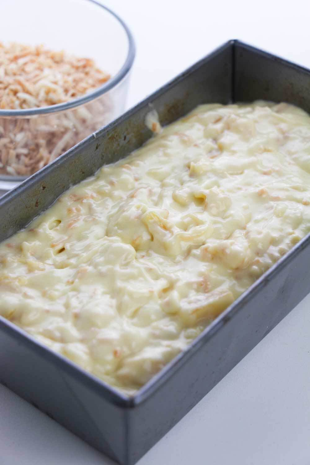 Hawaiian Desserts: Easy Pineapple Coconut Cake Recipe featured by top Hawaii blogger, Hawaii Travel With Kids: Pour the cake batter into the pan. Image of pineapple coconut cake batter in a loaf pan.