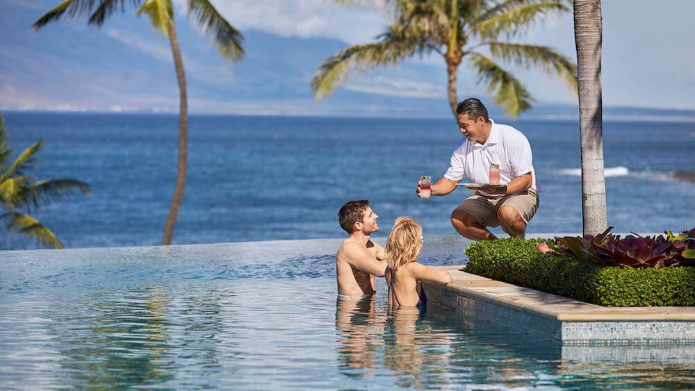 The Four Seasons Maui is just one of the top Maui Luxury Hotels worth checking out. Image of a couple in an infinity pool in Maui