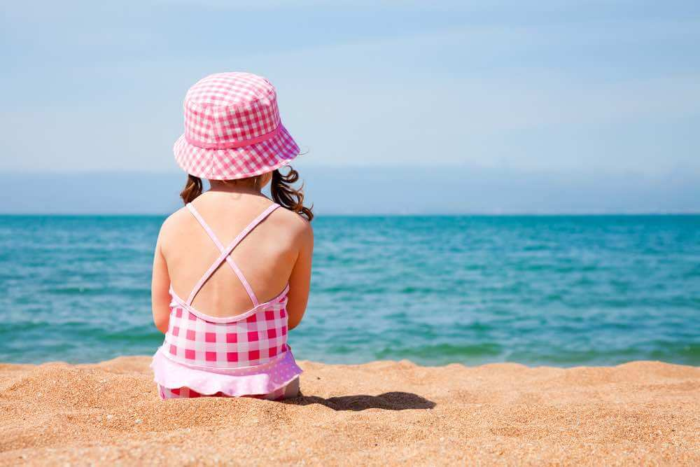 Find out he best kids sun hats recommended by top Hawaii blog Hawaii Travel with Kids. Image of a Girl sitting on beach wearing kids sun hat