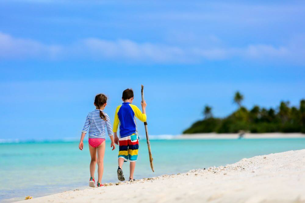 Find out the best kids rash guards for Hawaii by top Hawaii blog Hawaii Travel with Kids. Image of Little kids in rash guards for sun protection on tropical beach during summer vacation
