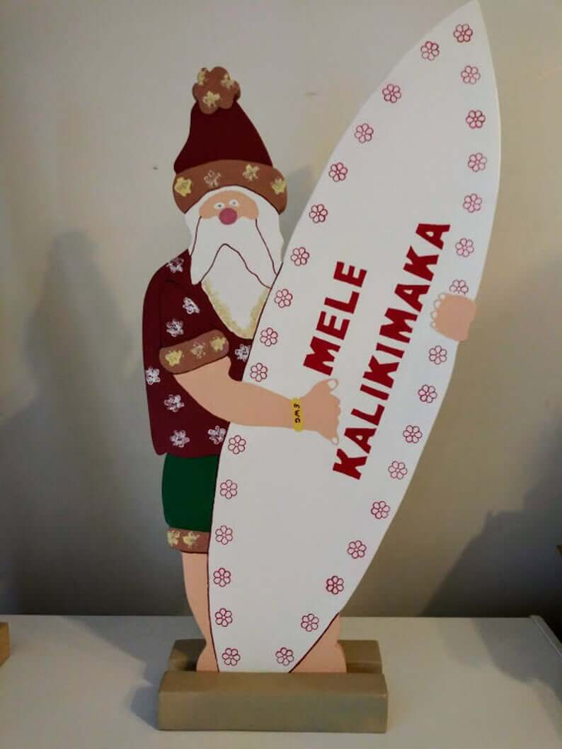 Best Hawaiian Christmas Decorations featured by top Hawaii blogger, Hawaii Travel with Kids: Add some Hawaiian Christmas decorations to your home this holiday season with these top Hawaii Christmas decorations ideas from top Hawaii blog Hawaii Travel with Kids. Image of Mele Kalikimaka Surfing Santa sign
