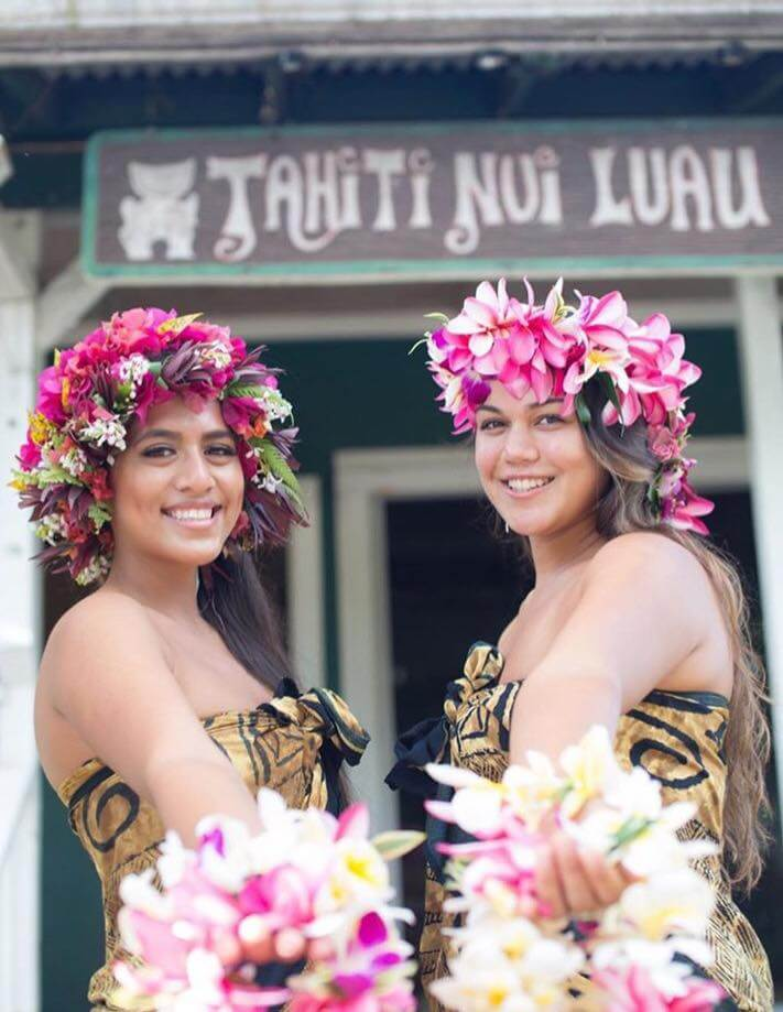 6 Best Kauai Luau Options featured by top Hawaii blogger, Hawaii Travel with Kids: Tahiti Nui has one of the best North Shore Kauai luau options. Image of two women holding leis in front of the Tahiti Nui restaurant