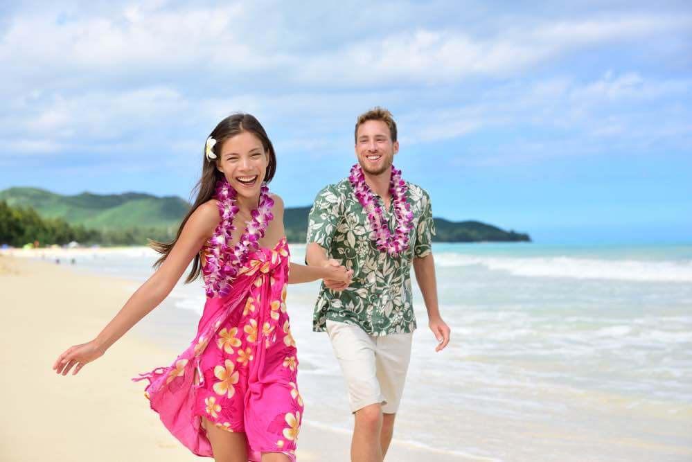 6 Best Kauai Luau Options featured by top Hawaii blogger, Hawaii Travel with Kids: Happy couple having fun running on Hawaii beach vacations in Hawaiian clothing wearing Aloha shirt and pink sarong sun dress and flower leis for traditional wedding or honeymoon concept.