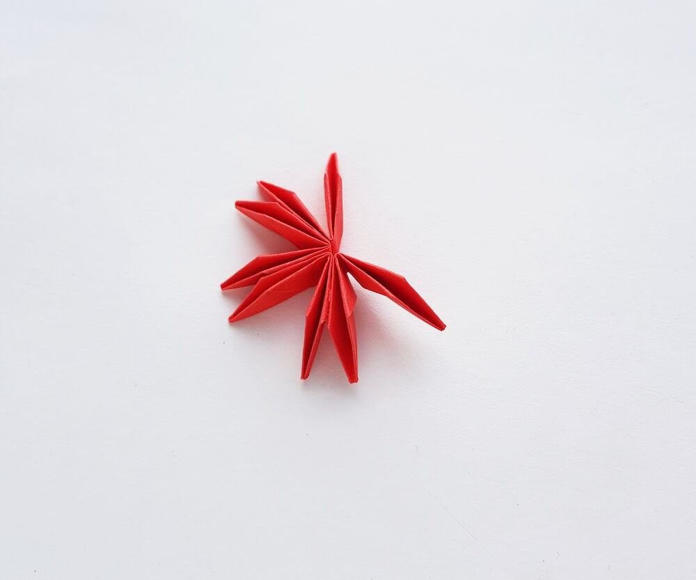 How to Make Origami Poinsettia Flowers, a Hawaiian Christmas craft tutorial featured by top Hawaii blogger, Hawaii Travel with Kids: Image of folded red paper that is glued together