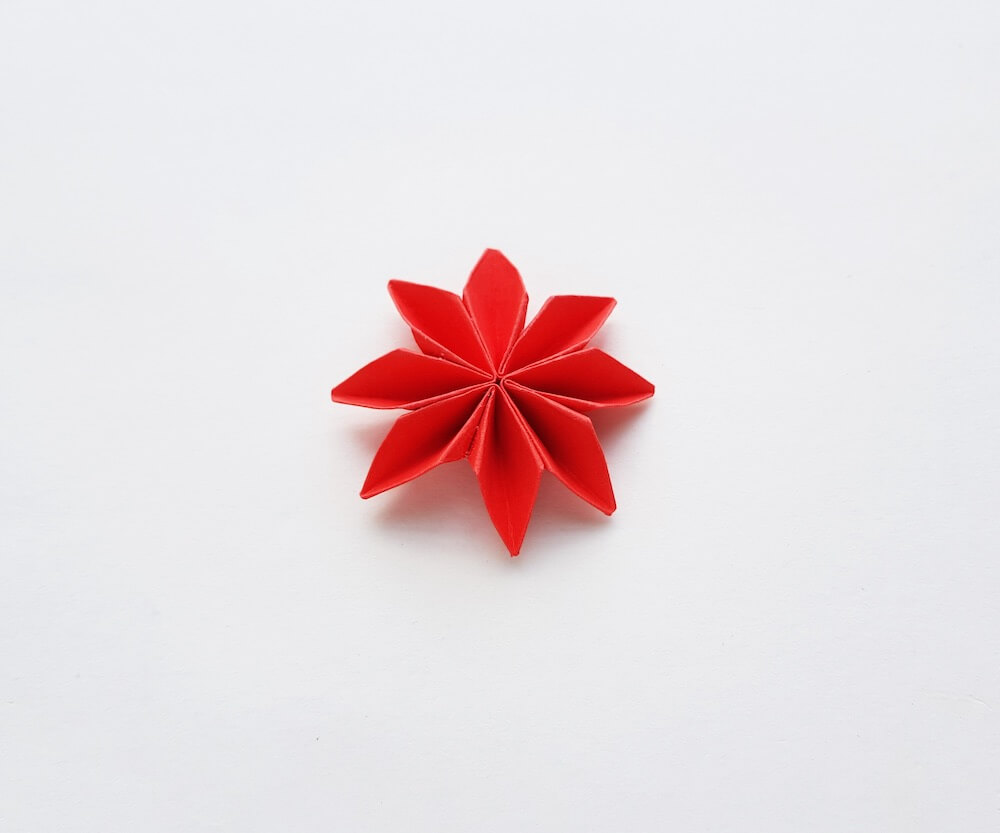 How to Make Origami Poinsettia Flowers, a Hawaiian Christmas craft tutorial featured by top Hawaii blogger, Hawaii Travel with Kids: Image of a paper poinsettia flower