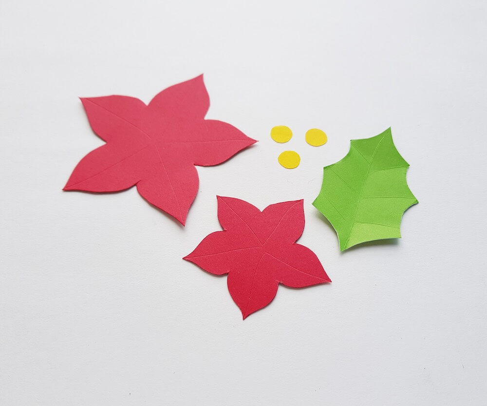 How to Make a Paper Poinsettia Craft, a tutorial featured by top Hawaii blog, Hawaii Travel with Kids: image of pieces of paper cut out and scored