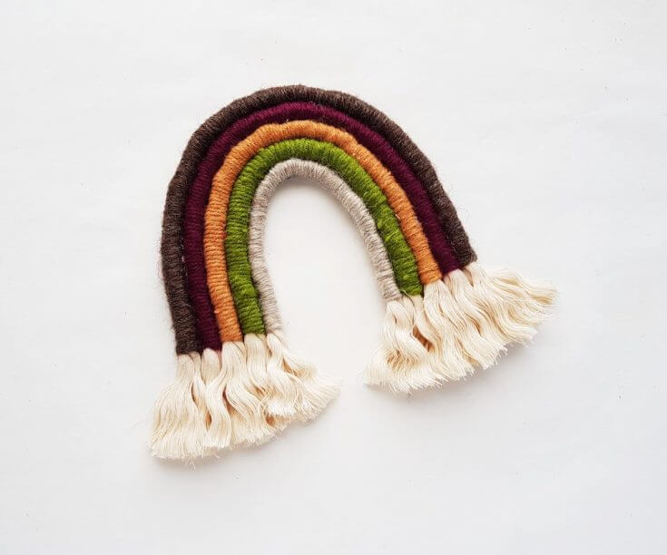 How to make a Rainbow Macrame wall hanging: image of a macrame rainbow wall hanging with frayed rope edges