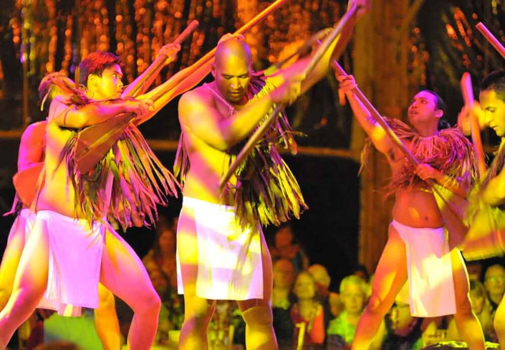 6 Best Kauai Luau Options featured by top Hawaii blogger, Hawaii Travel with Kids: Luau Kalamaku is one of the best Kauai luau. Image of men dancing with sticks
