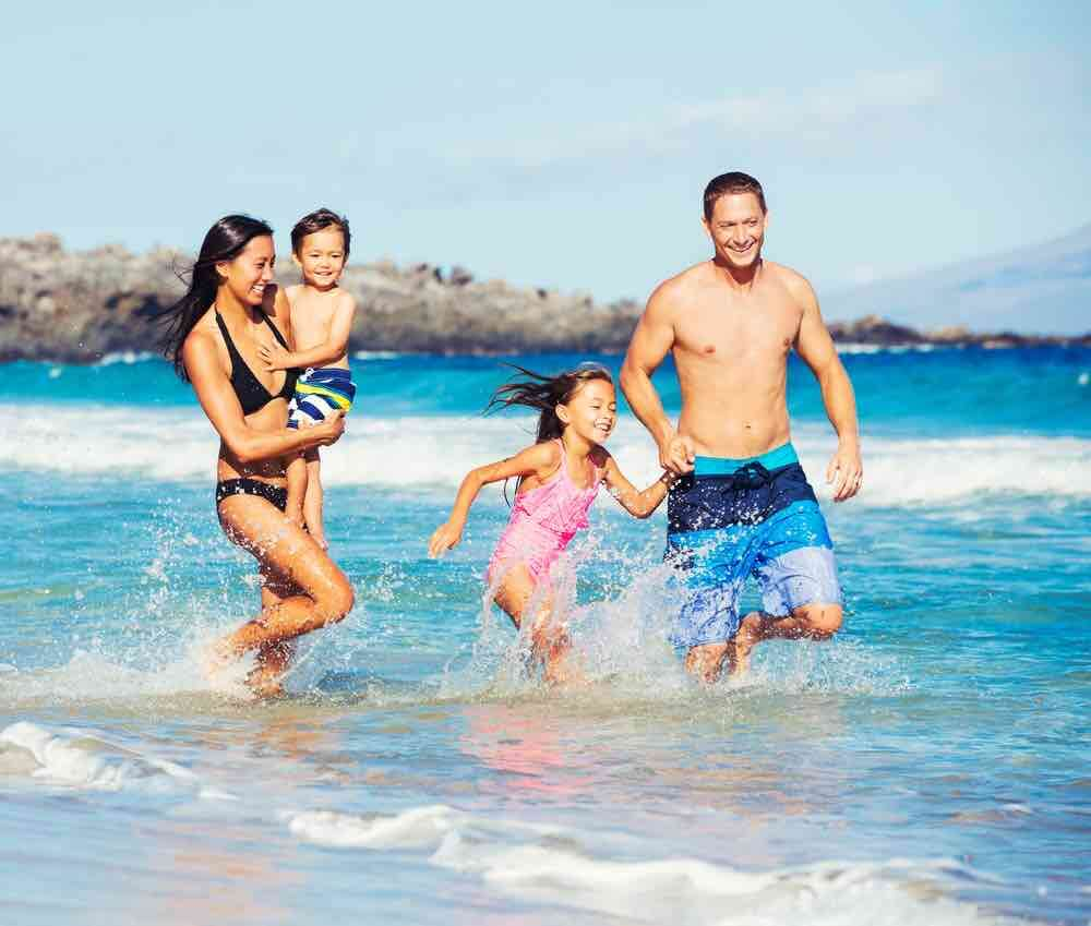 Heading to Hawaii in Winter? Find out the coolest things to do in Hawaii during the winter. Image of Young Happy Family Playing Having Fun at the Beach Outdoors