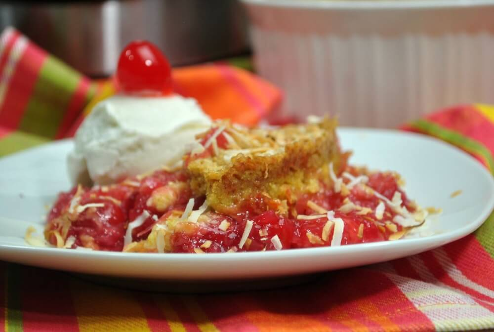 Learn how to make this easy Instant Pot Pina Colada Dump Cake by top Hawaii blog Hawaii Travel with Kids. Image of a pineapple coconut cake with ice cream and a cherry on top.