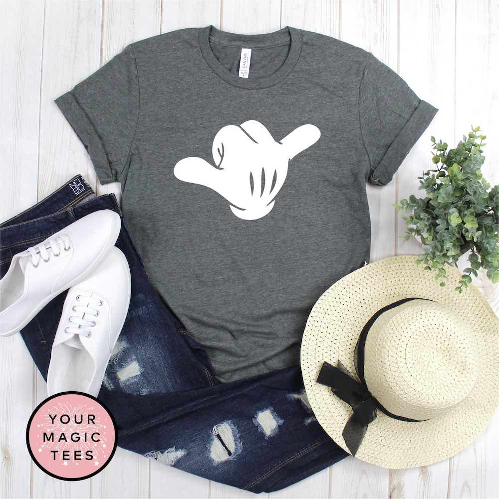 Find out the cutest Disney Aulani t-shirts to buy before your trip to Disney's Aulani Resort in Hawaii by top Hawaii blog Hawaii Travel with Kids. Buy this adorable shaka Disney shirt for your next trip to Aulani Resort. Image of a Mickey hand throwing a shaka sign.