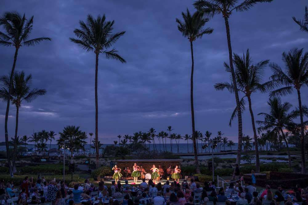 The Sunset Luau is a top Big Island luau at the Waikoloa Beach Marriott Resort and Spa. Image of a luau near resort pools and the ocean at dusk.