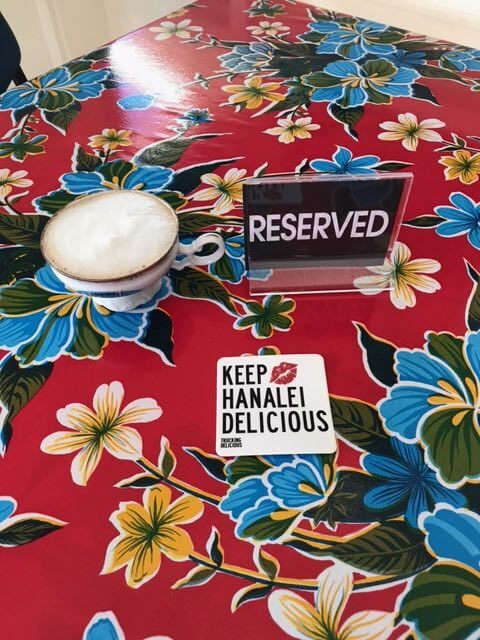 Trucking Delicious is an awesome Kauai food truck. Image of a reserved sign on a table with a sign that says keep Hanalei delicious.