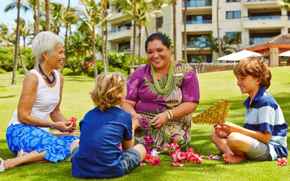 Best Maui Resorts for Families: Where to Stay on Maui with Kids featured by top Hawaii blog, Hawaii Travel with Kids: https://hawaiitravelwithkids.com/wp-content/uploads/2020/11/lei-making-hero.jpg