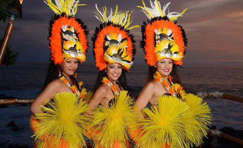 The Voyagers of the Pacific luau is a top Big Island luau to check out. It's at the Royal Kona Resort in Hawaii. Image of 3 Tahitian dancers posing.