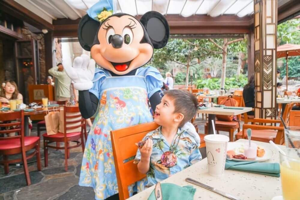 If you're looking for unique things to do with kids in Oahu, head to Aulani Resort to have breakfast with Mickey Mouse! Image of a boy smiling at Minnie Mouse.