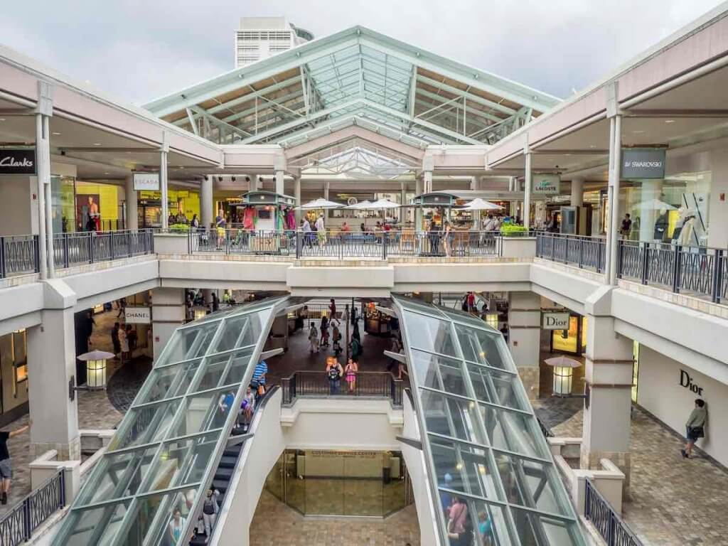 One of the best things to do in Oahu with teens is go shopping at Ala Moana Center. Image of an open air, 3 story mall in Hawaii.