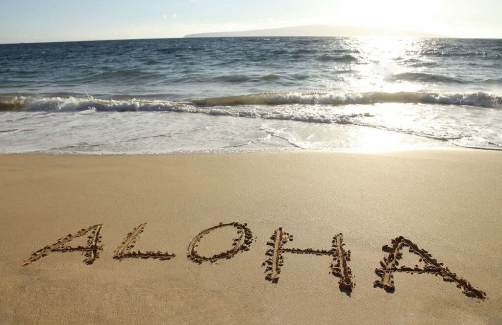 It helps to learn a few Hawaiian words before traveling to Hawaii for the first time. Image of the word Aloha written in the sand.