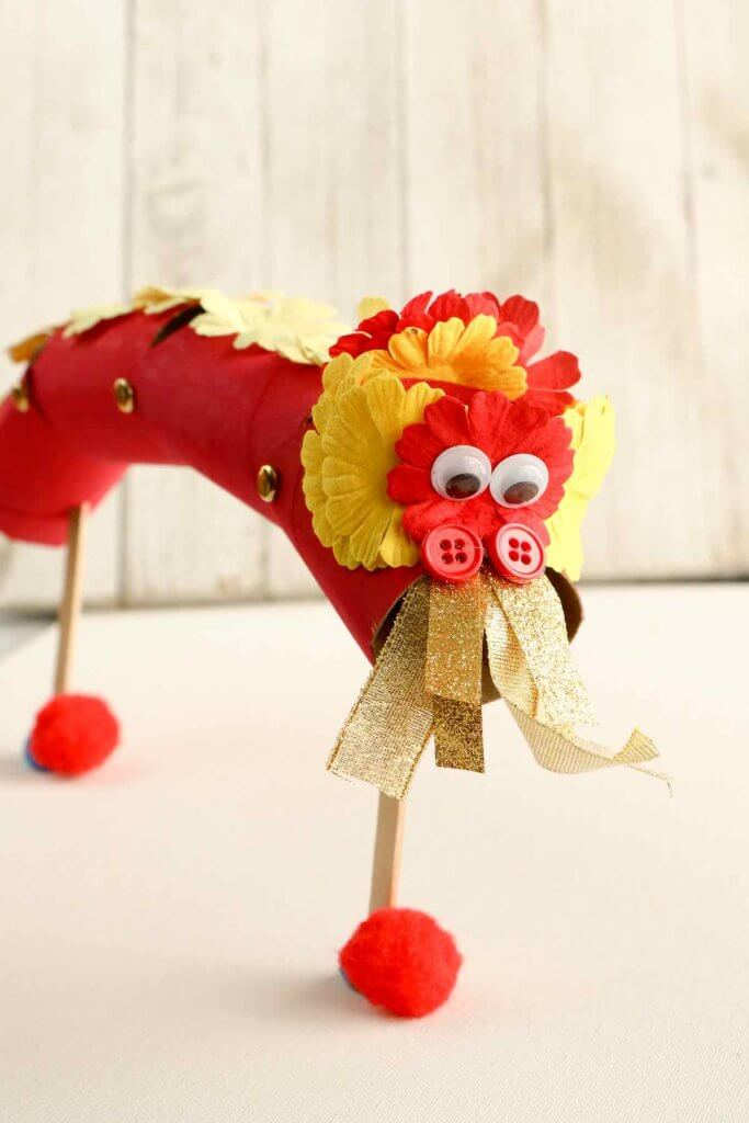 Learn how to make these Chinese New Year kids crafts by top Hawaii blog Hawaii Travel with Kids. Image of a Chinese Dragon Puppet.