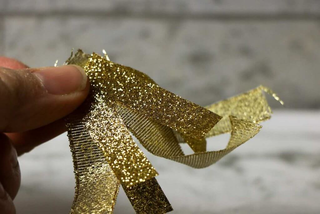 Cut the gold ribbon to make the flames for your Chinese New Year dragon puppet. Image of someone holding strips of gold ribbon.