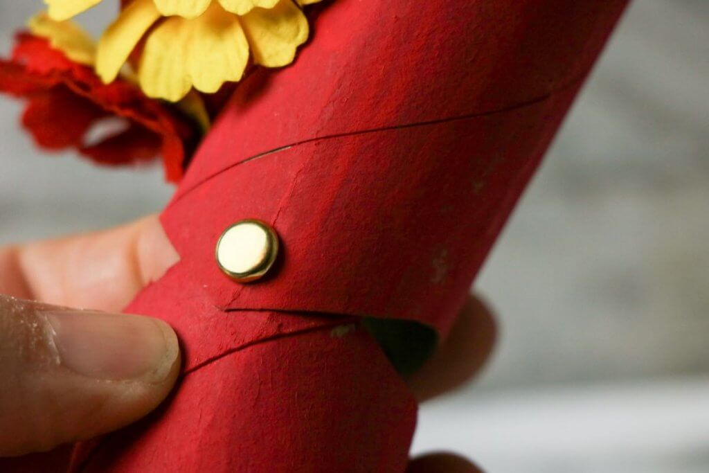 Attach the pieces of your Chinese dragon craft using brads. Image of a brad connecting two painted cardboard tubes.