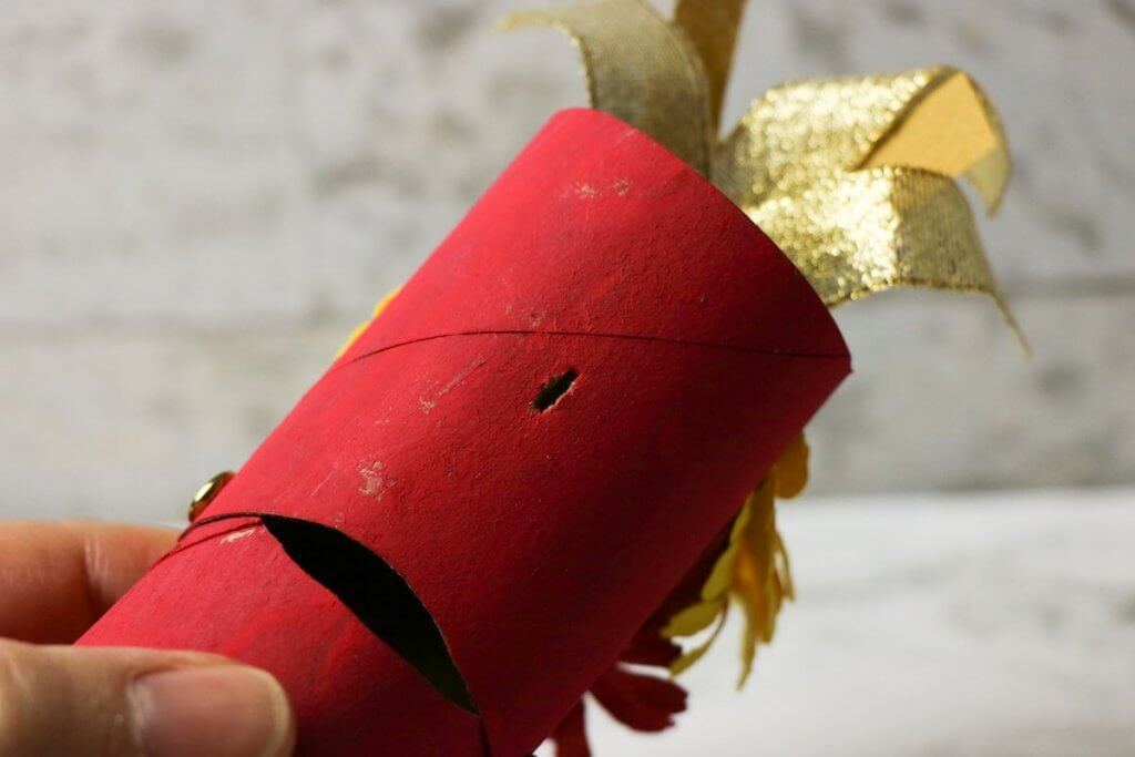 Cut a slit in the paper towel roll so you can turn it into a paper dragon puppet. Image of a red painted cardboard tube with a slit in it.