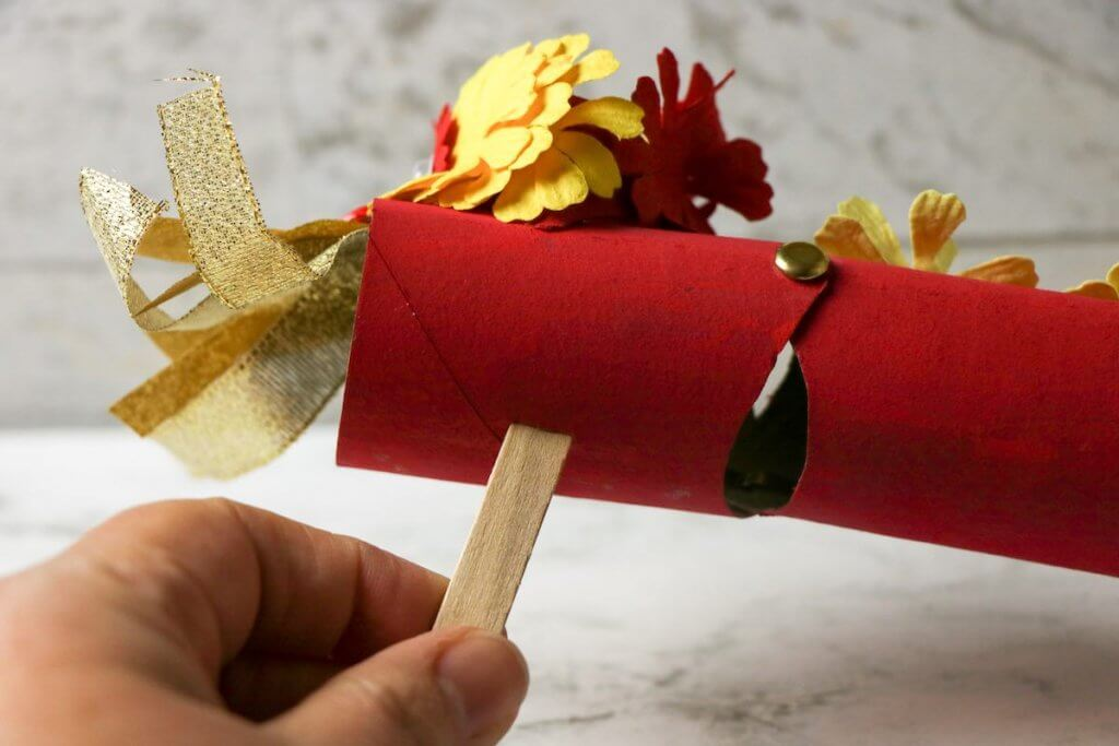 Insert the craft stick to make your Chinese dragon puppet. Image of a Chinese New Year dragon puppet out of cardboard.