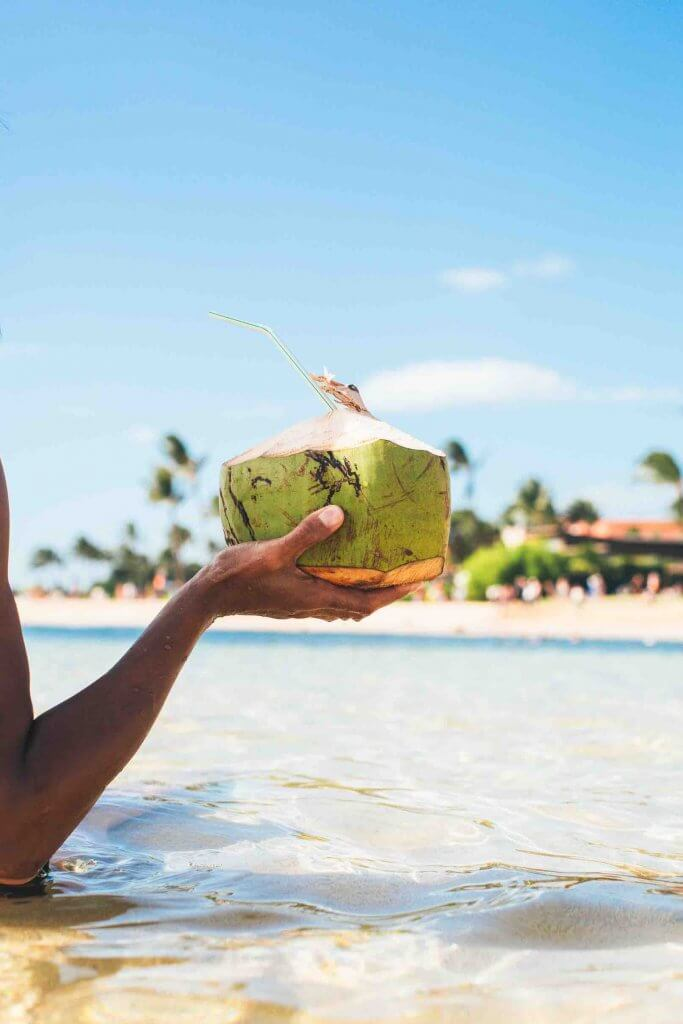 One of the best things to do in Oahu with kids is let them taste fresh coconut water. Image of a woman holding a fresh coconut at the beach.