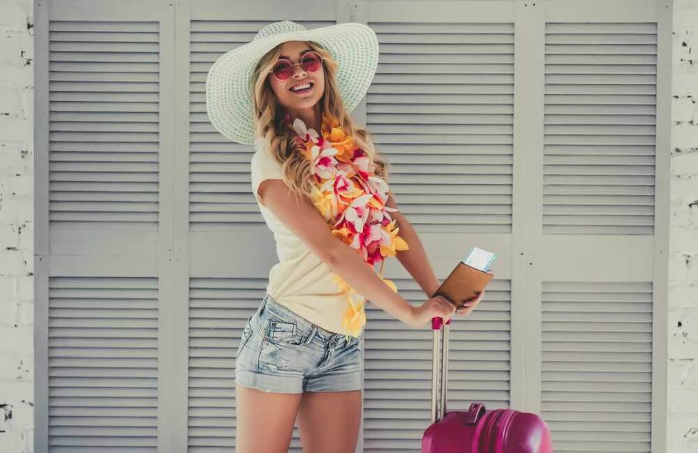 Planning a Hawaii trip and want to know know the best Hawaii travel advice? Find out what you need to know before booking your Hawaii vacation, espeically if it's your first time visiting Hawaii. Image of Attractive young woman is preparing for traveling. Standing on grey background with big suitcase in Hawaii accessories, pink sunglasses and hat with passport and ticket in hand.