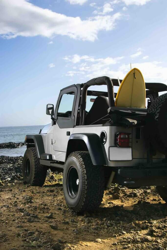 One of my top Maui tips for planning a trip to Maui is to rent a car. Image of SUV parked at beach with surfboard in Maui, Hawaii.