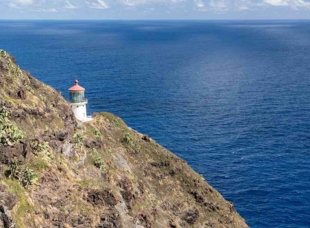 Makapuu Lighthouse is one of the coolest things to do in Oahu Hawaii with kids. Image of a lighthouse on a cliff by the ocean.
