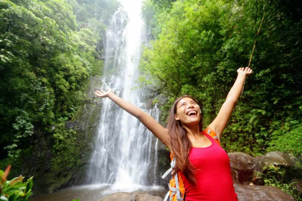 Find out all the best tips for planning a trip to Maui by top Hawaii blog Hawaii Travel with Kids. Image of Hawaii woman tourist excited by waterfall during travel on the famous road to Hana on Maui, Hawaii. Ecotourism concept image with happy backpacking girl. Mixed race Asian / Caucasian backpacker.