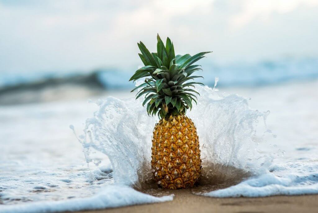 Find out whether you should use fresh or canned pineapple upside down rum cake. Image of a pineapple on the beach with waves crashing into it.