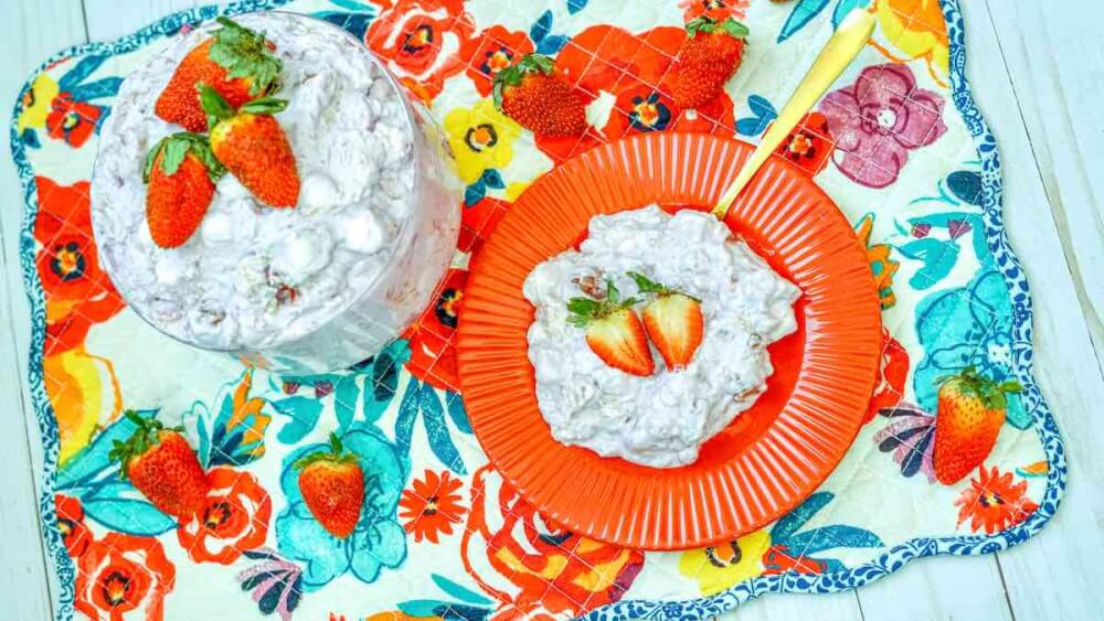 Learn how to make Strawberry Pineapple Cool Whip Salad by top Hawaii blog Hawaii Travel with Kids. Image of pink pineapple fluff.