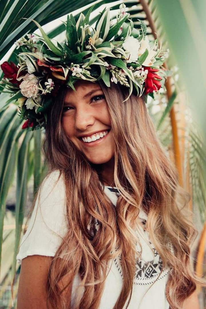 Making a flower lei crown is one of the most fun things to do on Oahu. Image of a woman wearing a lei po'o.