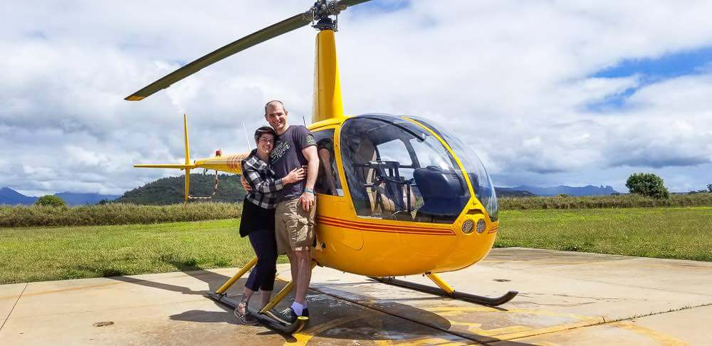 Find out whether or not a Kauai helicopter tour is worth it. Image of a man and woman posing in front of a yellow helicopter on Kauai.