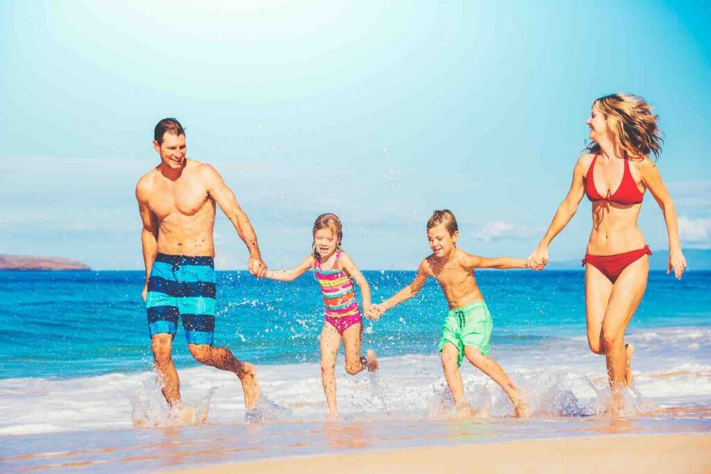 Find out the best 5 days in Maui interary for families from top Hawaii blog Hawaii Travel with Kids. Image of: Happy family having fun on beautiful warm sunny beach.