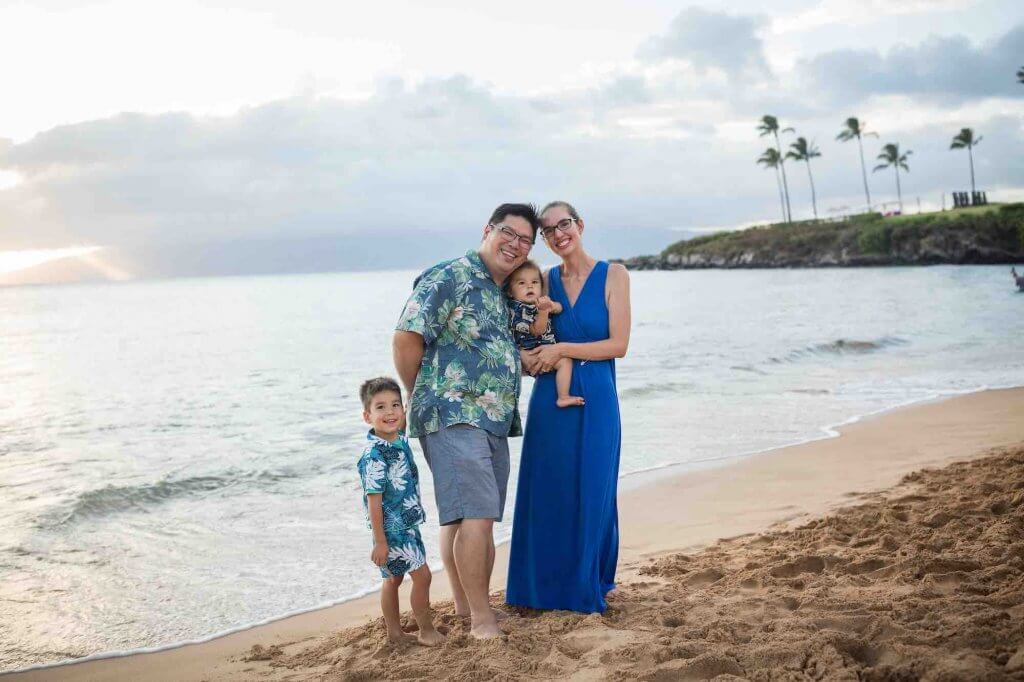 One of the best things to do in Maui with kids is do a professional photo shoot. Image of a family posing on the beach in Maui.