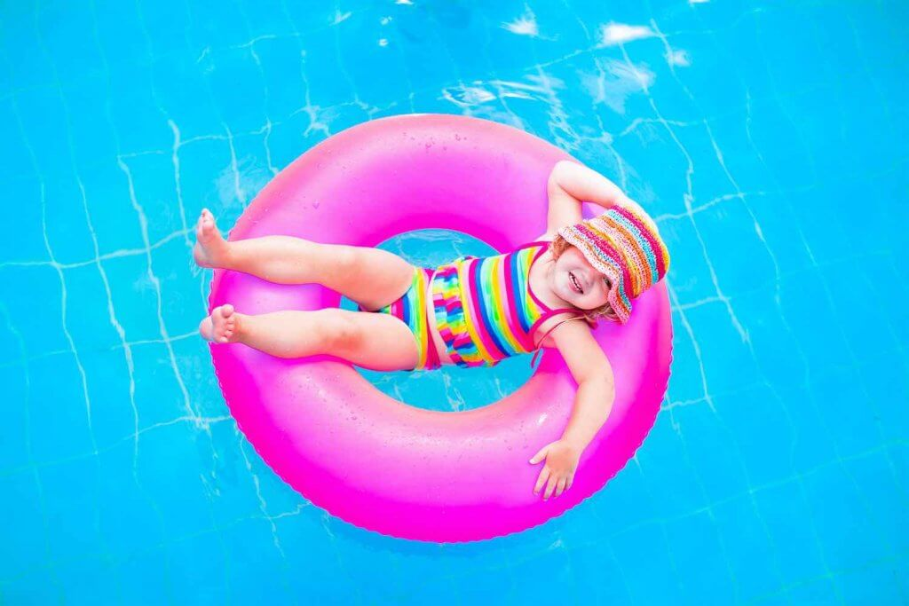 One of the top things to do in Maui with kids is play at the pool! Image of Cute funny little toddler girl in a colorful swimming suit and hat relaxing on an inflatable toy ring floating in a pool having fun during summer vacation in a tropical resort