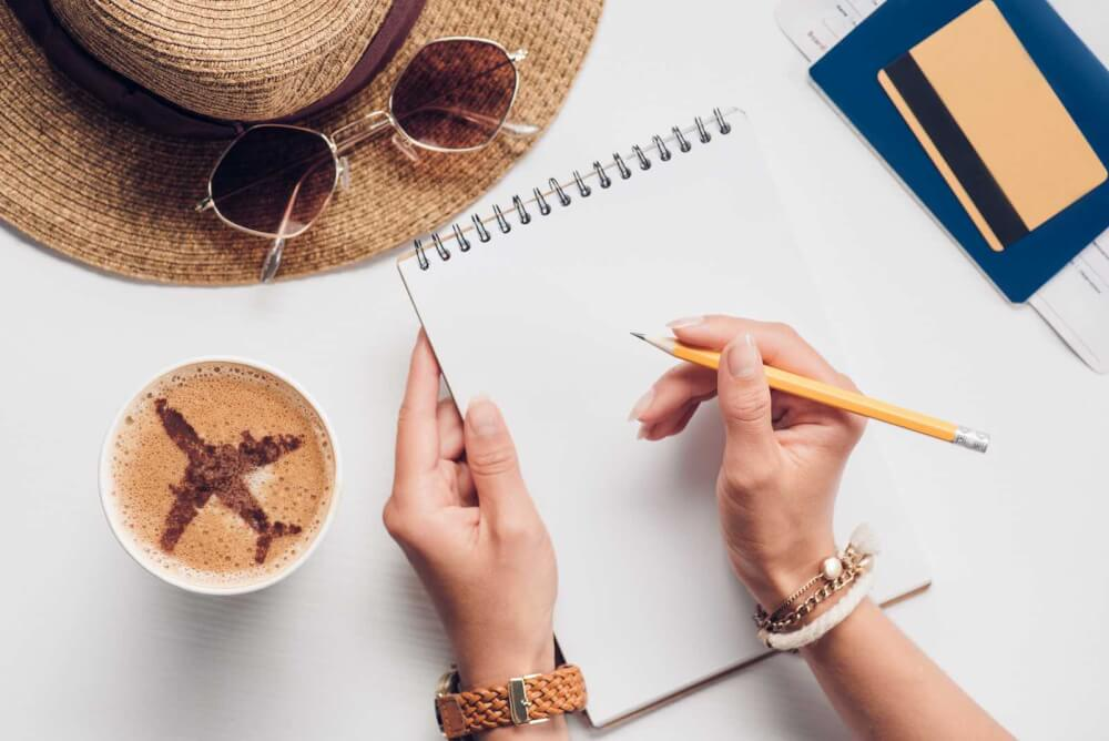 Find out 10 crucial Kauai vacation planning tips from top Hawaii blog Hawaii Travel with Kids. Image of a woman with a blank notebook surrounded by travel items.