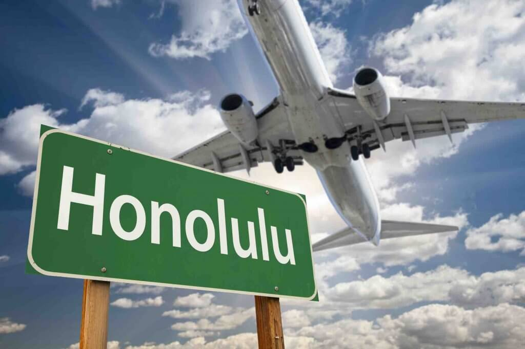 Check online for the best Hawaii flight deals. Image of Honolulu Green Road Sign and Airplane Above with Dramatic Blue Sky and Clouds.