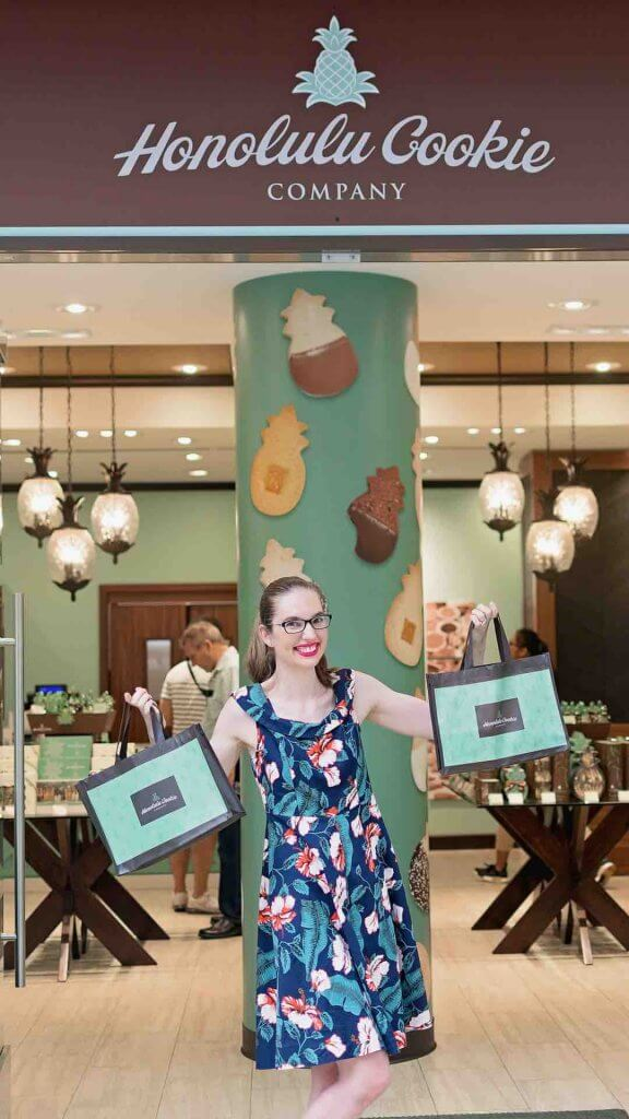 Enjoying Honolulu Cookie Company samples is one of my favorite free things to do Oahu. Image of a woman holding bags of Hawaiian cookies.