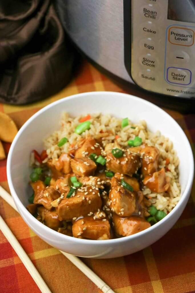 Quick and easy General Tso Chicken Instant Pot recipe. Image of a bowl of Chinese chicken over fried rice.