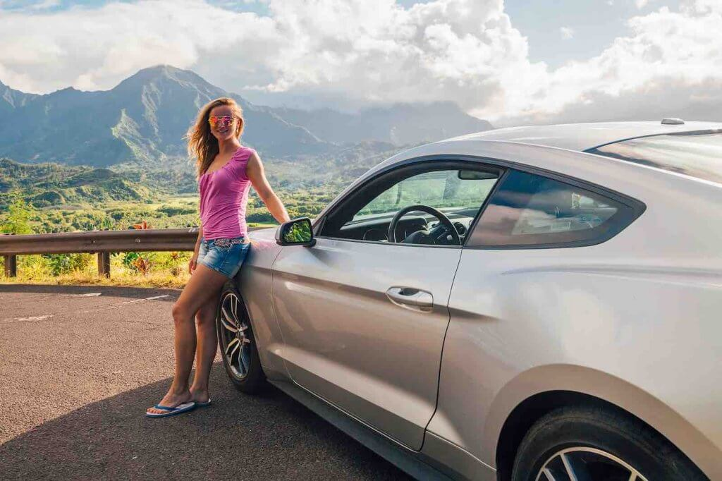One of my top tips for planning a trip to Kauai is to rent a car. Image of a woman posing by a rental car on Kauai.