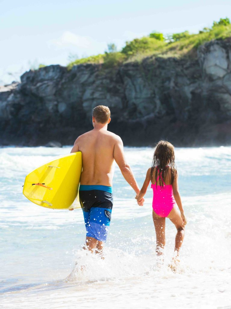 Find out all the best things to do in Kauai with kids by top Hawaii blog Hawaii Travel with Kids. Image of a father and daughter wearing swimsuits and walking in the ocean in Hawaii.