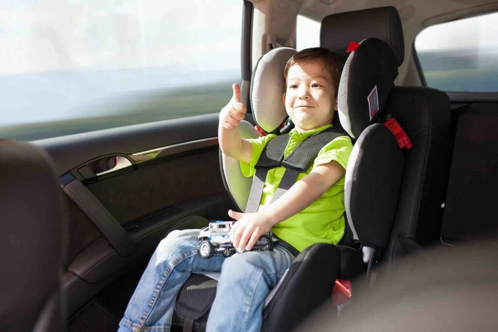 Image of a toddler in a car seat in a Hawaii rental car.