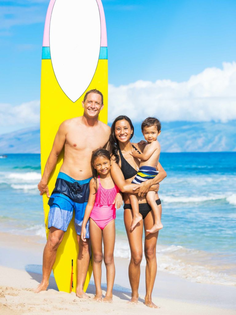Find out the best places to stay on Maui with kids by top Hawaii blog Hawaii Travel with Kids. Image of Happy Family with Surfboards on Tropical Beach with a yellow surfboard in the background.