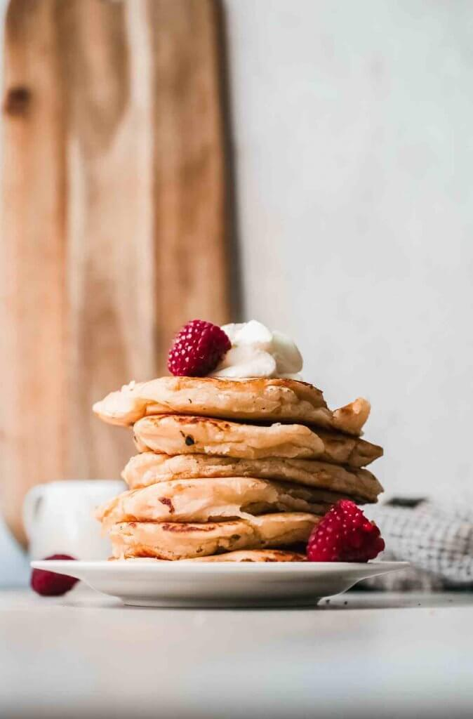 This recipe for rice flour pancakes is a slam dunk! Image of a plate stacked with 6 mochi pancakes and topped with whipped cream and fresh raspberries.
