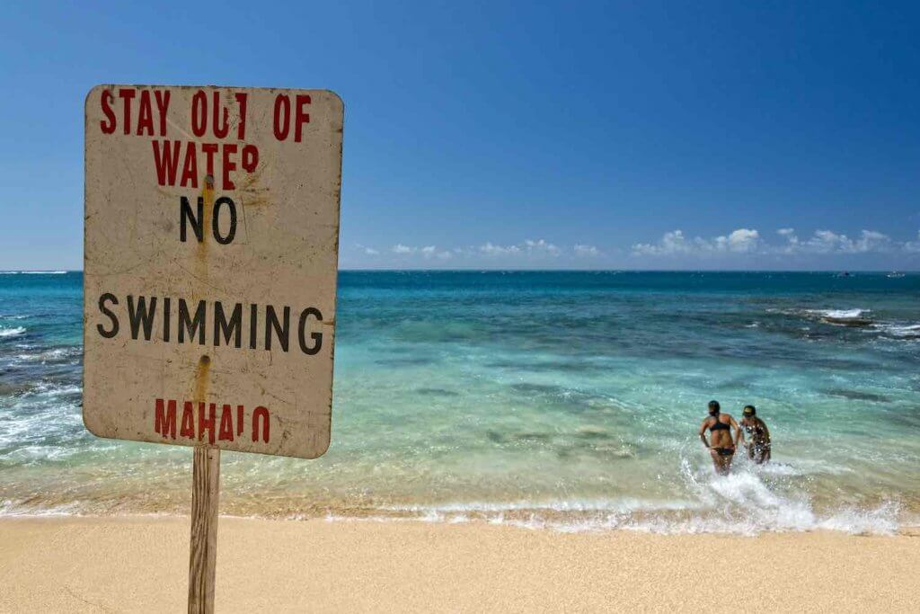 Look out for beach warning signs in Hawaii. Image of a No Swimming sign at a Hawaii beach with 2 people in the water behind the sign.