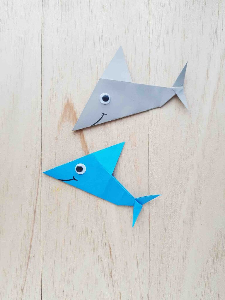 Get my easy origami shark instructions. Image of blue and grey origami sharks with googly eyes.